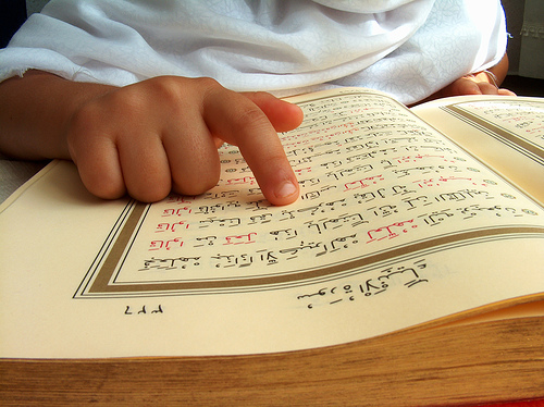 A child point his finger at the Mushaf - The One Who Struggles in Recitation