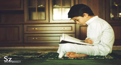 A little boy is reading the Qur'an.