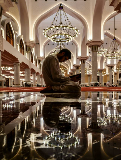 a Muslim recites the Qur'an while being in the mosque - people of Allah